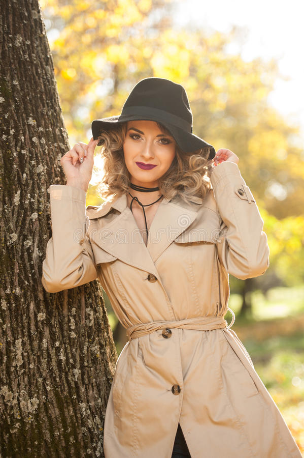 Beautiful blonde woman with cream coat , long legs and black hat in a autumn scene . Portrait of a very beautiful young Elegant and sensual woman with curly stock photos