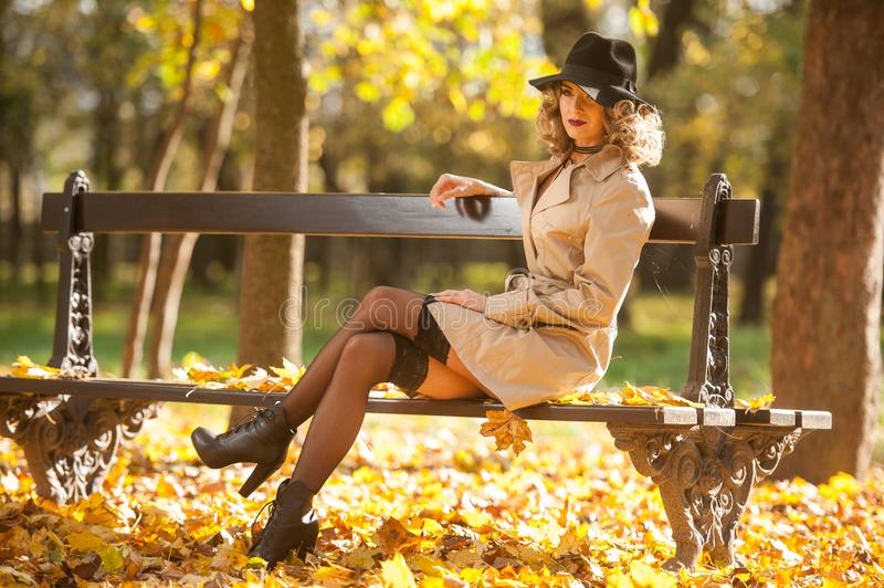Beautiful blonde woman with cream coat , long legs and black hat in a autumn scene . Portrait of a very beautiful Elegant and sensual woman with curly hair ans royalty free stock photos
