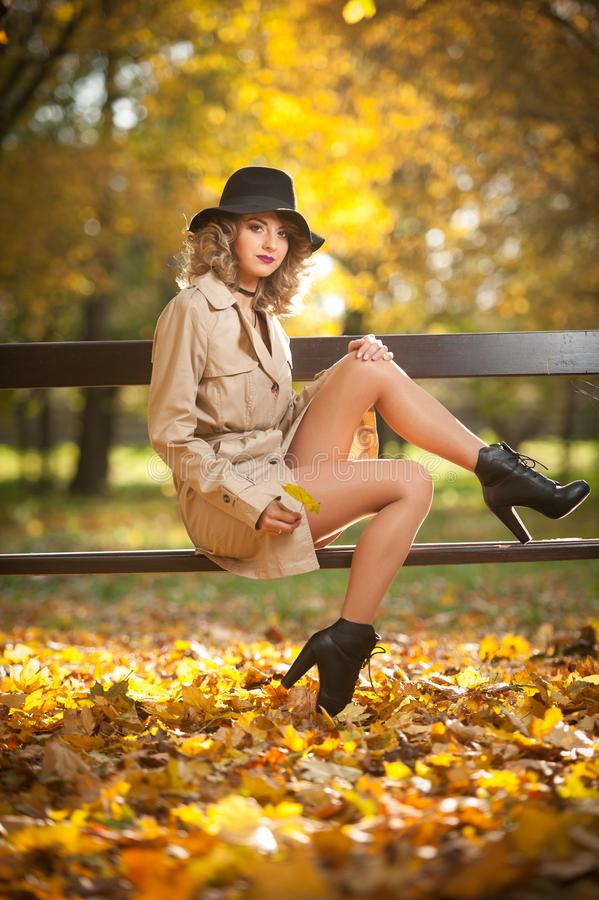 Beautiful blonde woman with cream coat , long legs and black hat in a autumn scene . Portrait of a very beautiful Elegant and sensual woman with curly hair ans royalty free stock photography