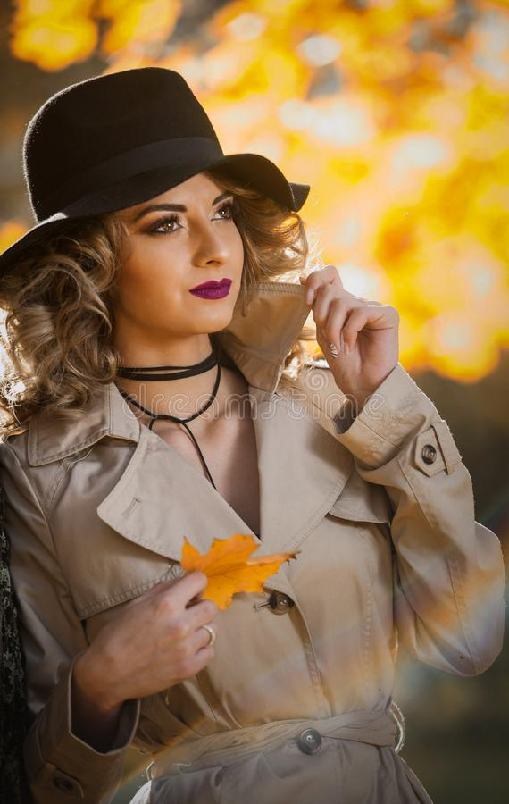 Beautiful blonde woman with cream coat , long legs and black hat in a autumn scene .Portrait of a very beautiful young Elegant and. Sensual woman with curly stock photos