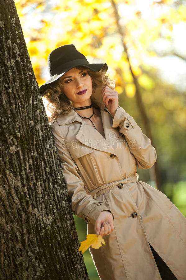 Beautiful blonde woman with cream coat , long legs and black hat in a autumn scene . Portrait of a very beautiful young Elegant and sensual woman with curly stock images