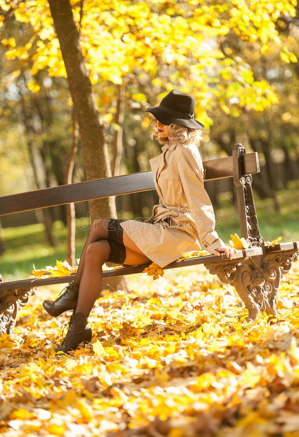 Beautiful blonde woman with cream coat , long legs and black hat in a autumn scene . Portrait of a very beautiful Elegant and sensual woman with curly hair ans stock photos