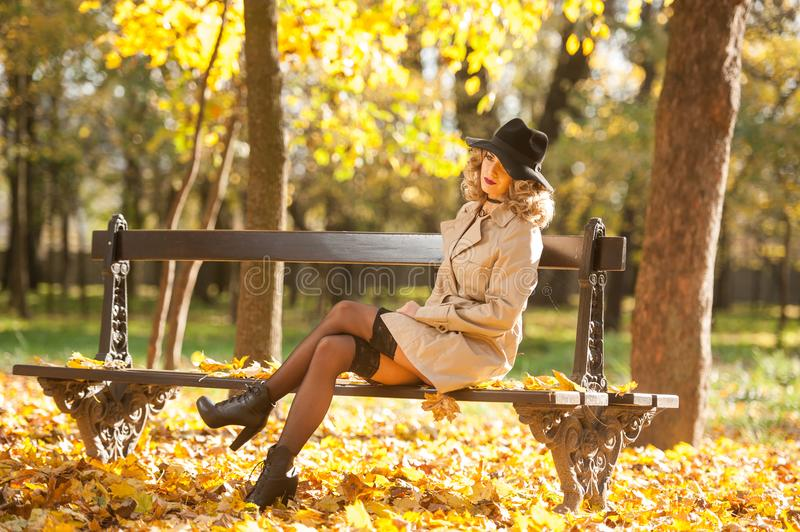 Beautiful blonde woman with cream coat , long legs and black hat in a autumn scene . Portrait of a very beautiful Elegant and sensual woman with curly hair ans stock photo