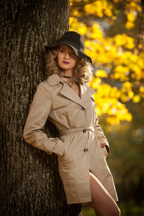 Beautiful blonde woman with cream coat , long legs and black hat in a autumn scene . Portrait of a very beautiful Elegant and sensual woman with curly hair ans stock image
