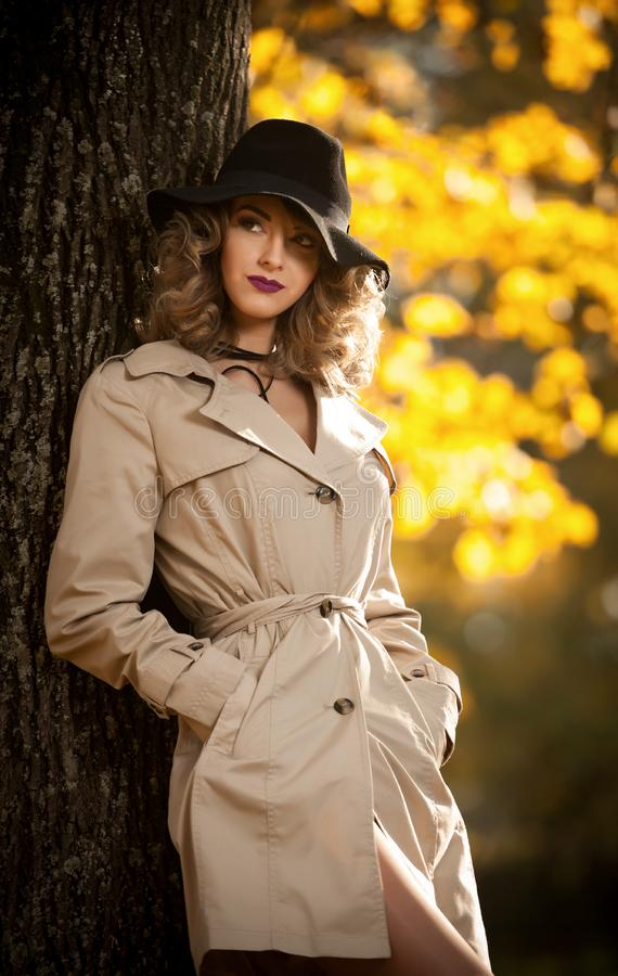Beautiful blonde woman with cream coat , long legs and black hat in a autumn scene .Portrait of a very beautiful young Elegant and. Sensual woman with curly royalty free stock photo