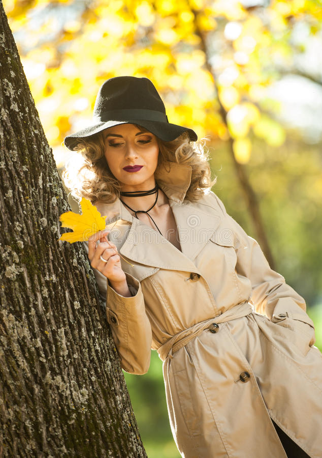 Beautiful blonde woman with cream coat , long legs and black hat in a autumn scene . Portrait of a very beautiful young Elegant and sensual woman with curly royalty free stock photos