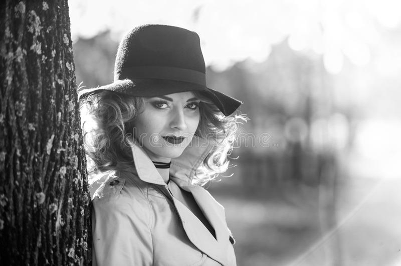 Beautiful blonde woman with cream coat , long legs and black hat in a autumn scene . Portrait of a very beautiful young Elegant and sensual woman with curly stock image