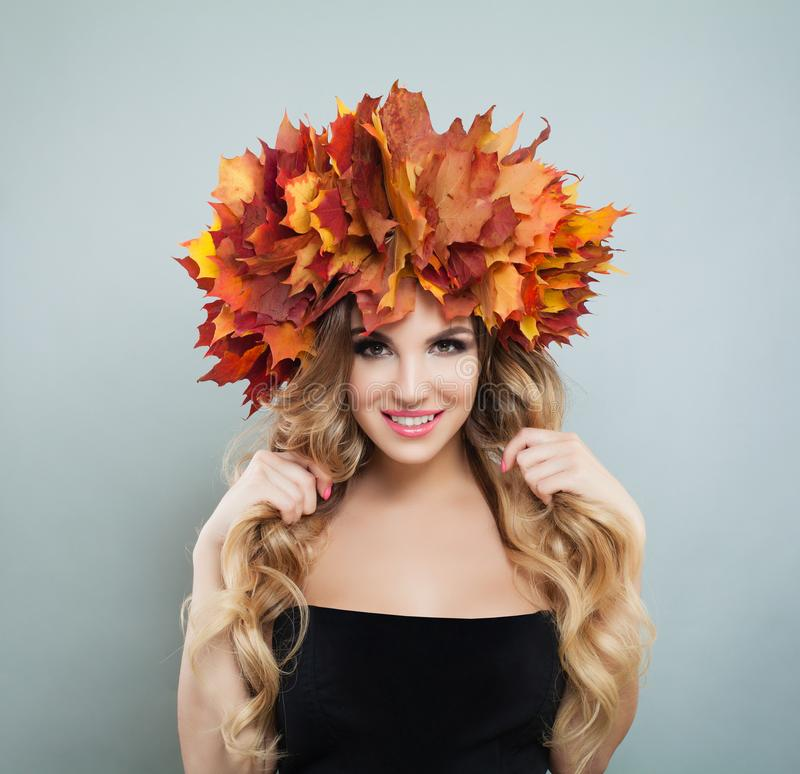 Beautiful blonde woman with curly hair, makeup and autumn leaves crown on gray background.  royalty free stock image