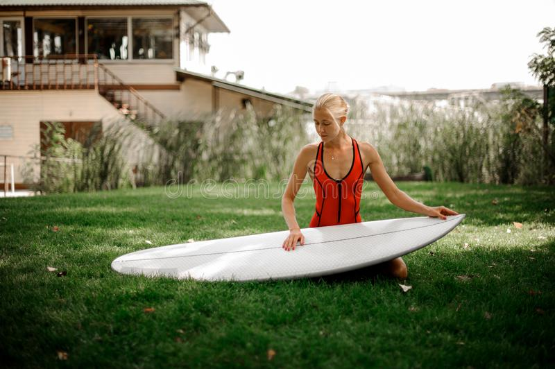 Beautiful blonde woman sitting on green lawn with a wakeboard. Beautiful blonde woman dressed in red swimsuit sitting on green lawn with a wakeboard on warm day royalty free stock images