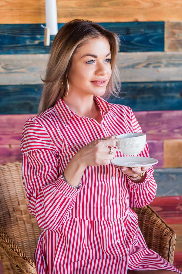 Beautiful blonde woman drinking coffee or tea in the morning and smiling. Lifestyle, happiness stock photo
