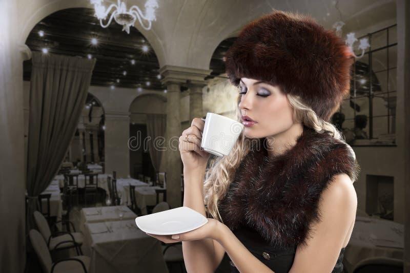 Beautiful blonde woman drinking a smoking hot stock photography