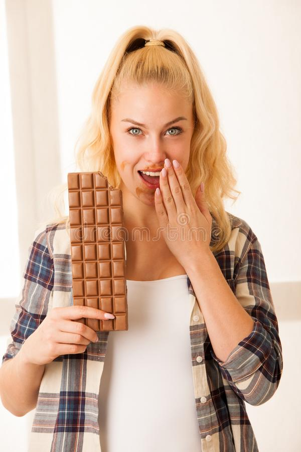 Beautiful blonde woman eats a big chocolate stock photo