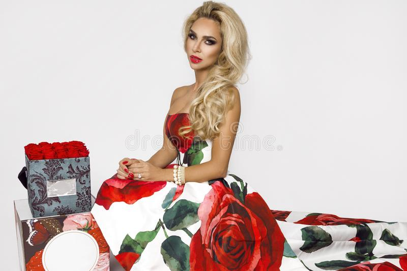 Beautiful blonde woman in an elegant evening gown with red roses, holding a Valentine`s gift, a flowerbox with flowers. Beauty. Beautiful blonde girl woman in an stock photography