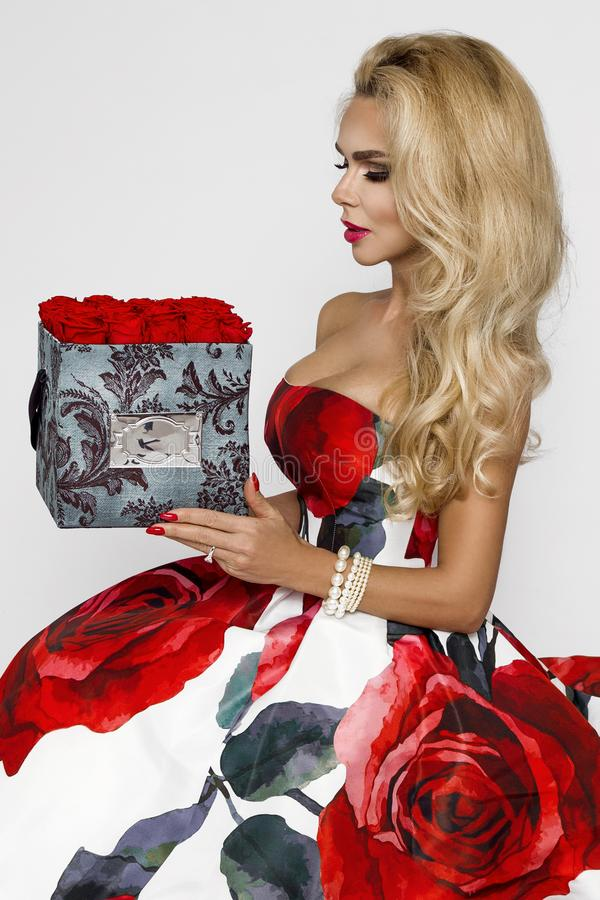 Beautiful blonde woman in an elegant evening gown with red roses, holding a Valentine`s gift, a flowerbox with flowers. Beauty. Beautiful blonde girl woman in an stock image