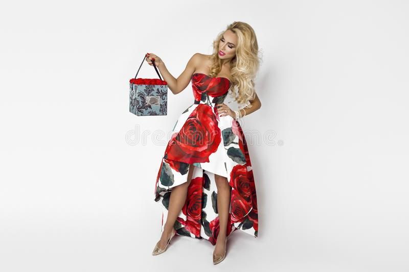 Beautiful blonde woman in an elegant evening gown with red roses, holding a Valentine`s gift, a flowerbox with flowers. Beauty. Beautiful blonde girl woman in an royalty free stock images