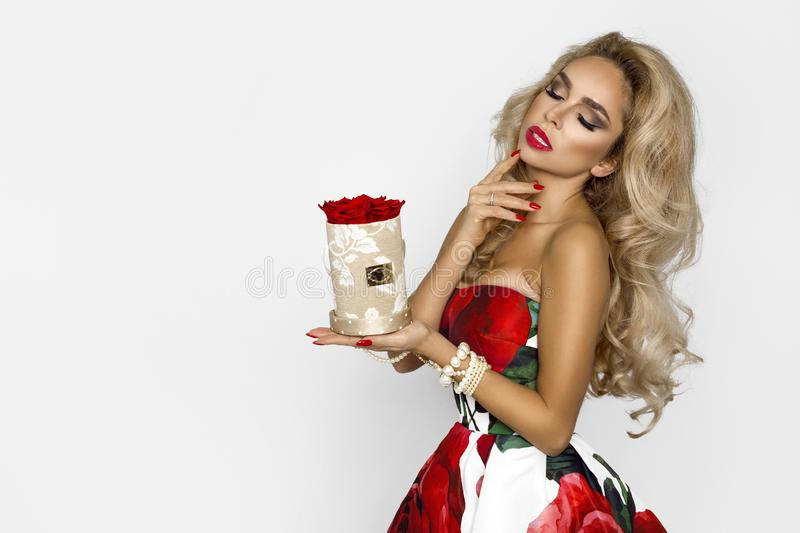Beautiful blonde woman in an elegant evening gown with red roses, holding a Valentine`s gift, a flowerbox with flowers. Beauty. Beautiful blonde girl woman in an stock photo