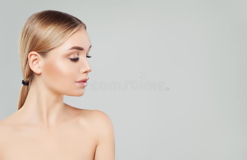 Beautiful blonde woman face, female profile on white background. Facial treatment, skin care and cosmetology concept stock photography