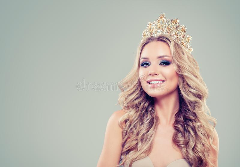 Beautiful blonde woman fashion model with long curly hair, makeup and gold crown on background with copy space royalty free stock photography