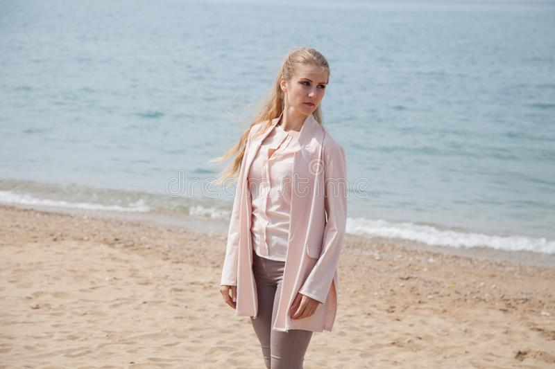Beautiful blonde woman walking on the sandy sea-Beach royalty free stock photography