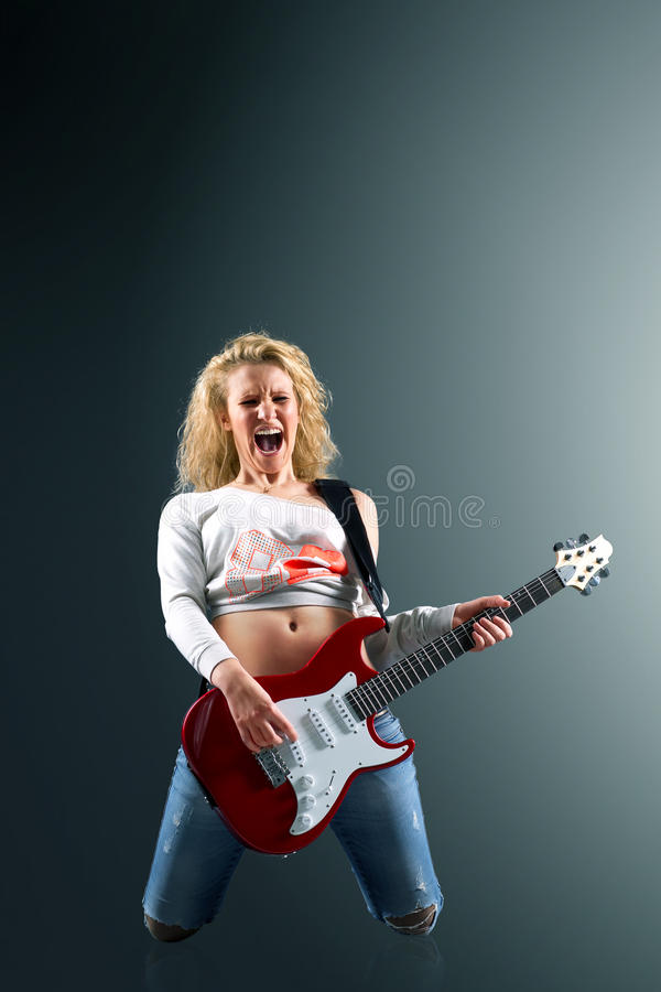 Beautiful blonde woman with a guitar sings a rock song royalty free stock photos