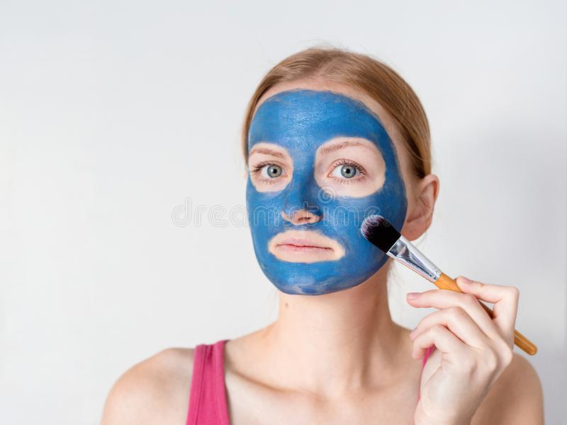 Beautiful blonde woman having blue clay facial mask apply by beautician. royalty free stock photos