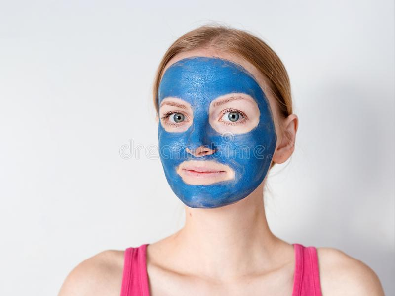 Beautiful blonde woman having blue clay facial mask apply by beautician. stock images