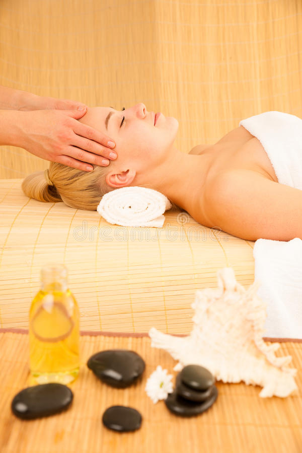Beautiful blonde woman having a face massage in spa salon royalty free stock photos