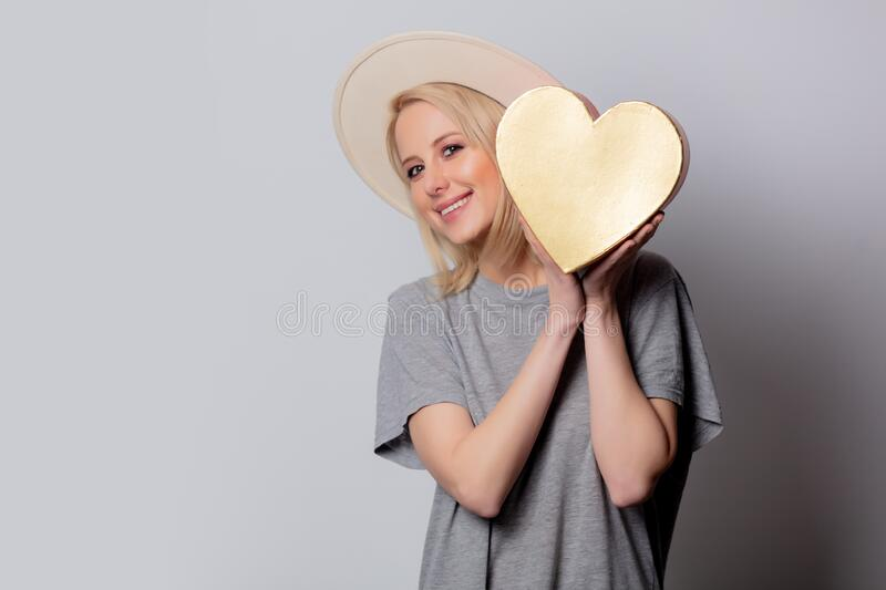 Beautiful blonde woman with heart shape box on white background stock photography
