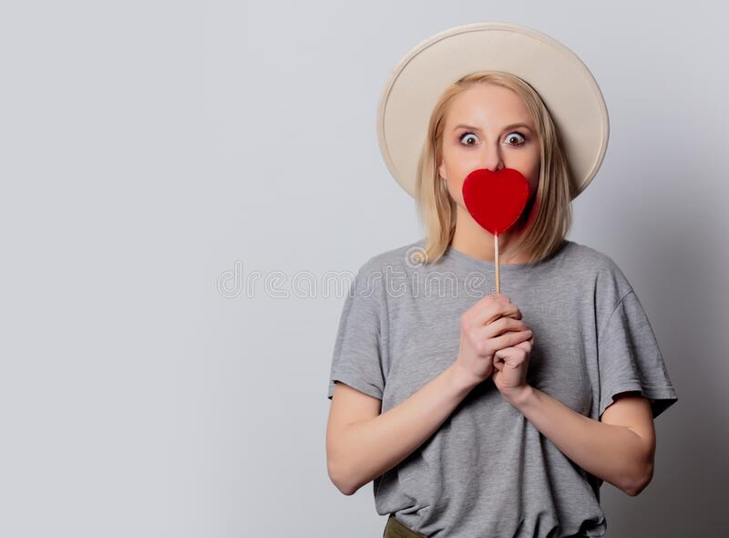 Beautiful blonde woman with heart shape candy on white background stock photo