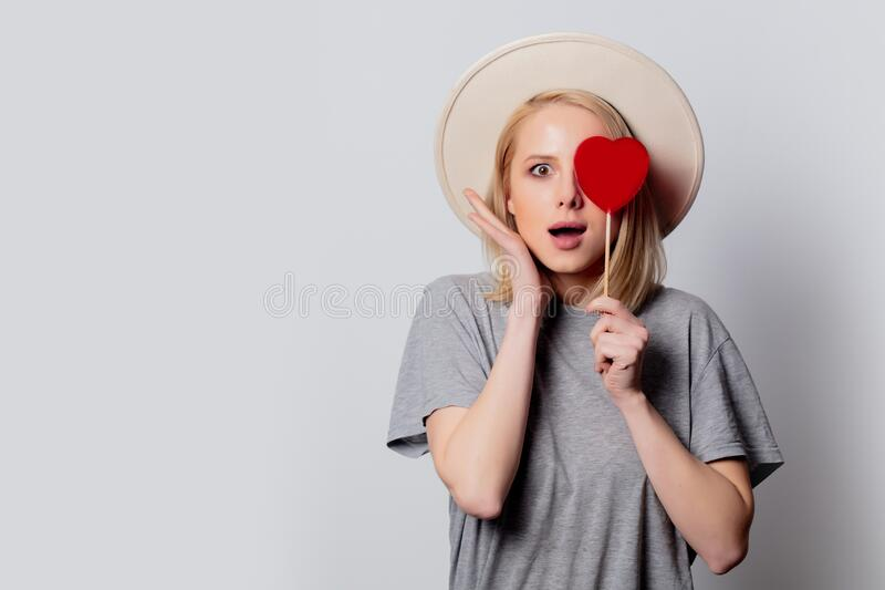Beautiful blonde woman with heart shape candy on white background stock image