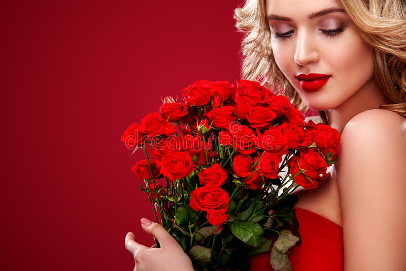 Beautiful blonde woman holding bouquet of red roses. Saint Valentine and International Women`s Day, Eight March stock photos