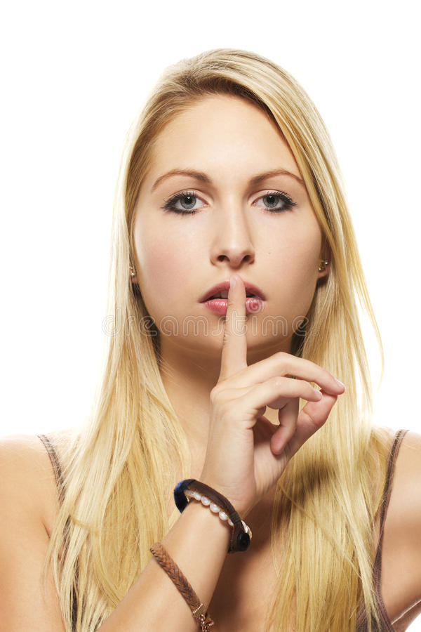 Beautiful blonde woman holding finger at her mouth royalty free stock image