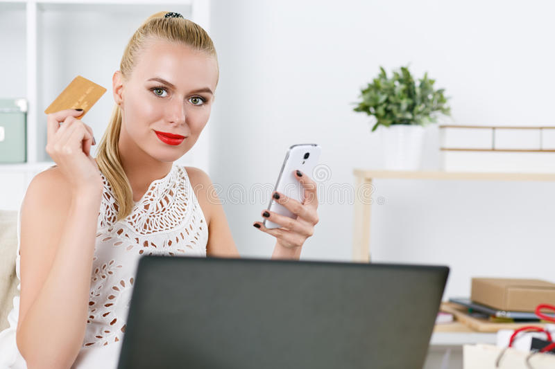 Beautiful blonde woman holding golden credit card. And cellphone looking in camera. Young lady buying dresses and new stuff in house via internet. Shopping stock photography