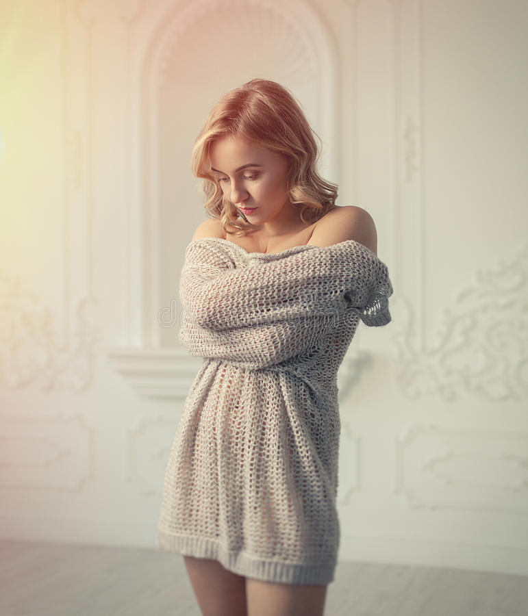 Beautiful blonde woman hugging herself in white interior stock image