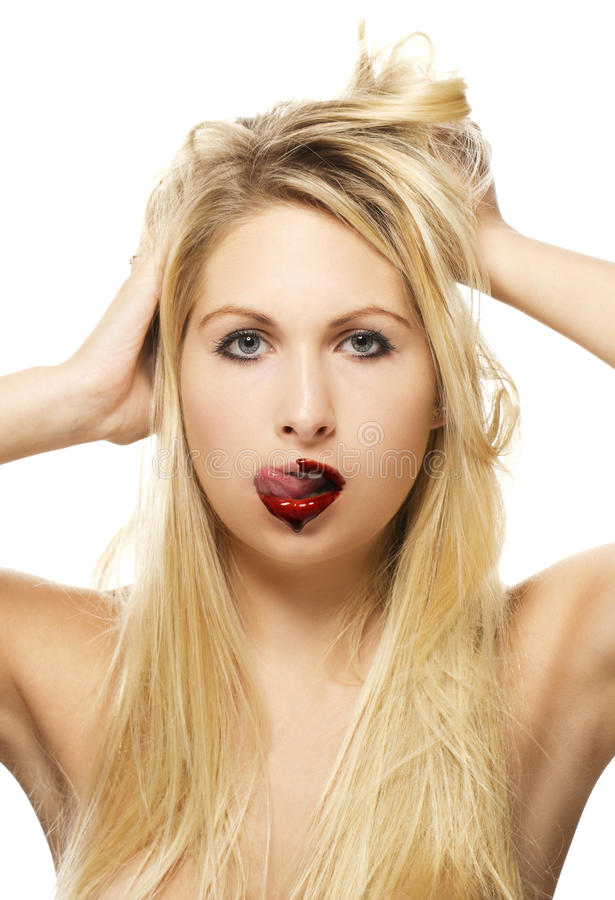 Beautiful blonde woman licking chocolate from her royalty free stock images