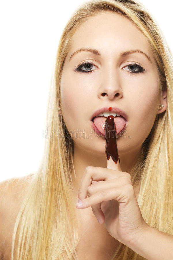 Beautiful blonde woman licking on her chocolate co stock photo