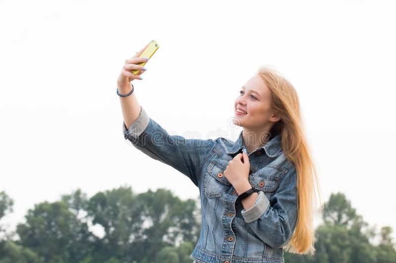 Beautiful blonde woman with long hair and in jeans with a smile makes a selfie on the background of nature. And the sky stock photos