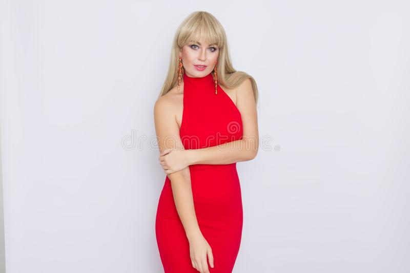 Beautiful blonde woman with long hair in red evening dress over grey background. Wearring on celebration. Sweet beautiful blonde woman with long hair in red royalty free stock photos