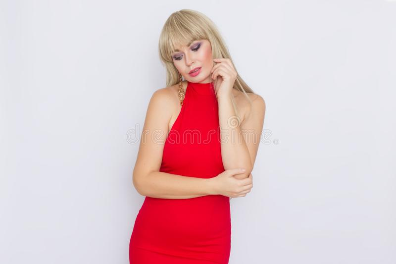 Beautiful blonde woman with long hair in red evening dress over grey background. Wearring on celebration. Sweet beautiful blonde woman with long hair in red stock photography