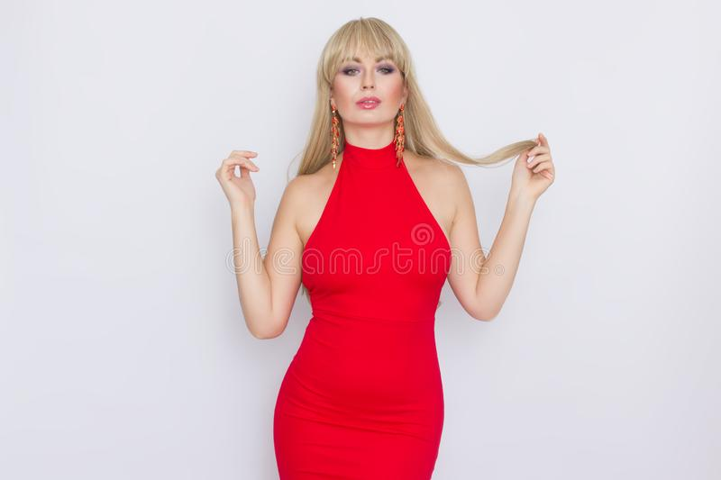 Beautiful blonde woman with long hair in red evening dress over grey background. Wearring on celebration. Sweet beautiful blonde woman with long hair in red stock photo