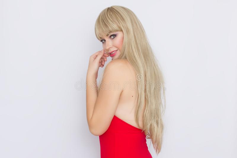 Beautiful blonde woman with long hair in red evening dress over grey background. Wearring on celebration. Sweet beautiful blonde woman with long hair in red royalty free stock image