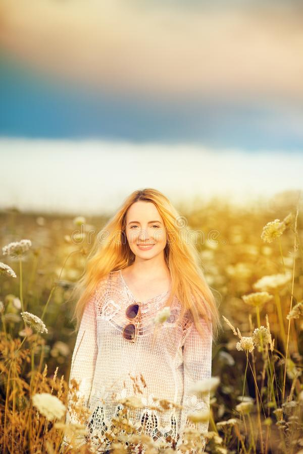 Beautiful blonde woman with long hair standing in a rural flower field outdoors royalty free stock images