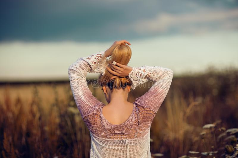 Beautiful blonde woman with long hair standing in a rural flower field outdoors, raising her hair stock photo
