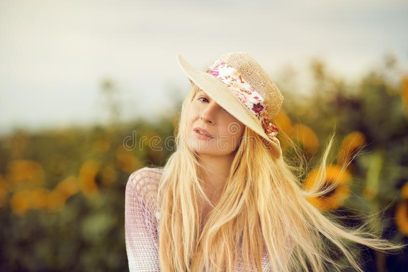 Beautiful blonde woman with long hair and sunhat in a rural sunflowers field royalty free stock photos