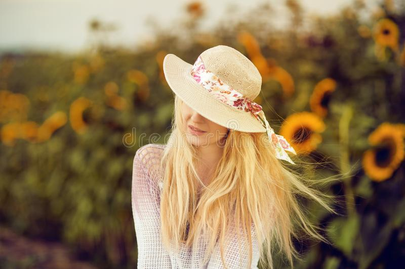 Beautiful blonde woman with long hair and sunhat in a rural sunflowers field stock image