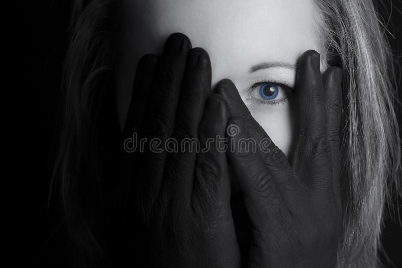 Beautiful blonde woman looking through fingers of black hand on stock photography