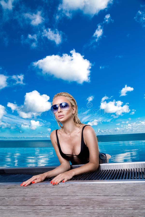 Beautiful blonde woman model with wet hair and elegant makeup sitting in a pool with amazing views in a luxury hotel, wearing jewe stock photo
