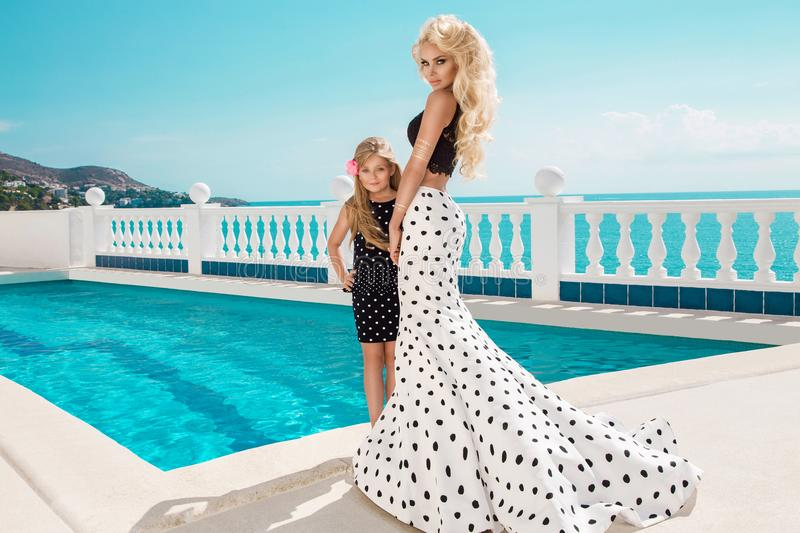 Beautiful, blonde woman, mother with daughter in an elegant polk royalty free stock photos