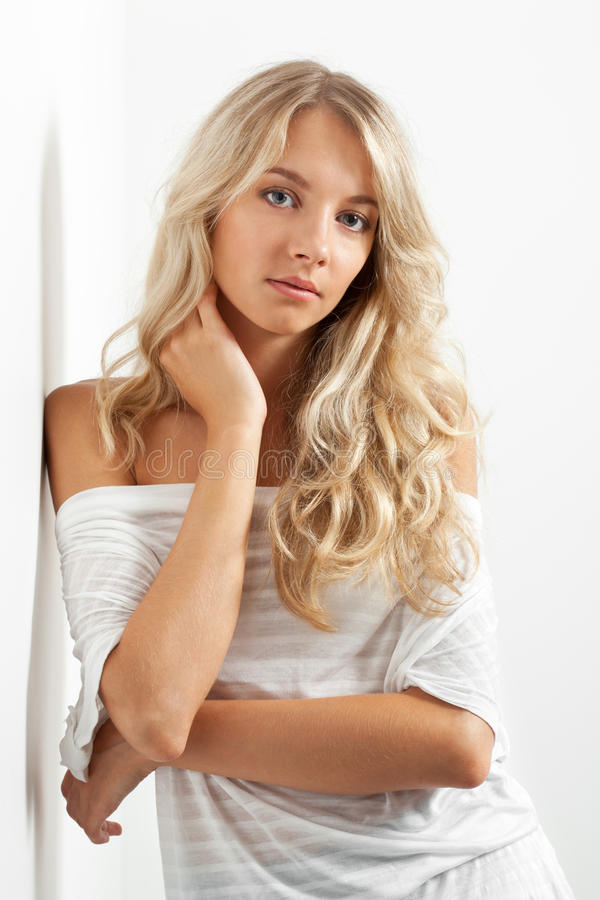 Beautiful blonde woman near white wall royalty free stock image