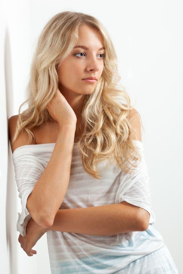Beautiful blonde woman near white wall stock photo